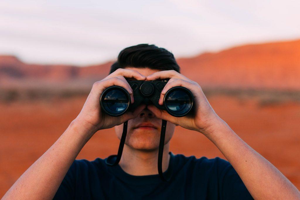 człowiek patrzący przez lornetkę